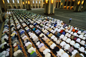 A group of Muslims praying together in the mosque.