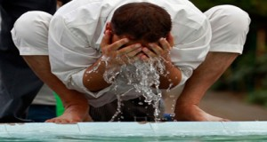 A person is performing Ablution with running water.