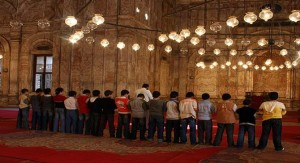 Some children are offering prayer behind an imam in a mosque.