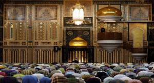 Some people are offering prayer in a mosque.
