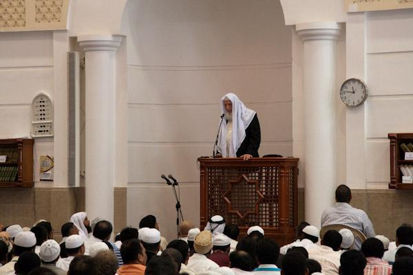 The imam is on the pulpit delivering Friday Khutbah.