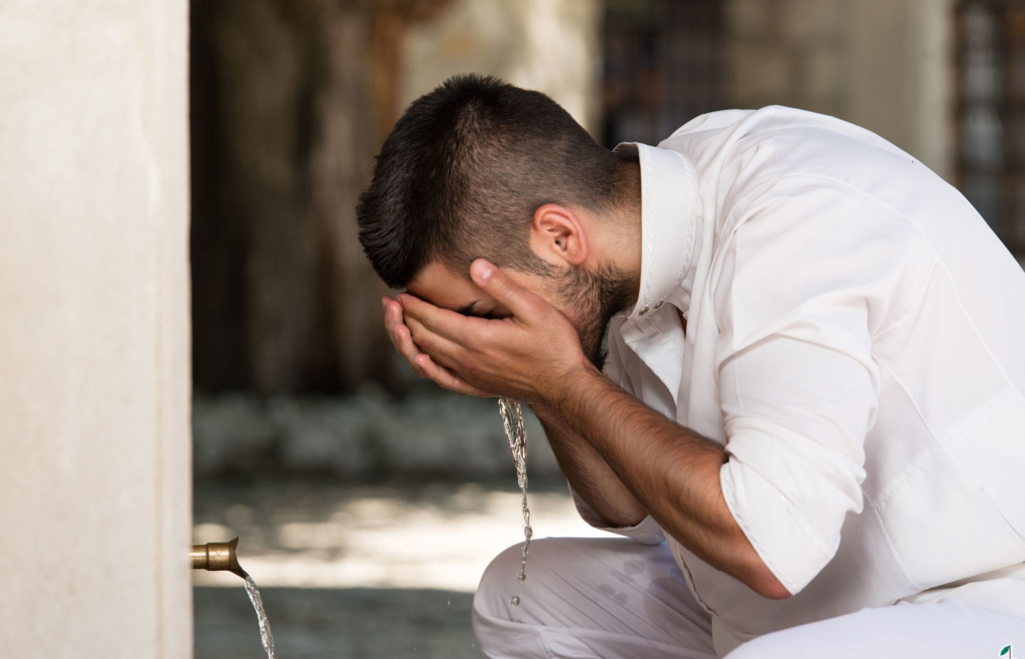 someone washes his face during ablution.